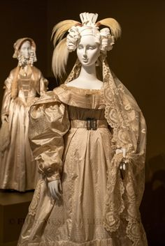 (foreground) Circa 1828 silk jacquard and aerophane Wedding Ensemble; (background) Circa 1845 silk satin, organza, and braid Wedding Ensemble.  Via FIDM Museum.