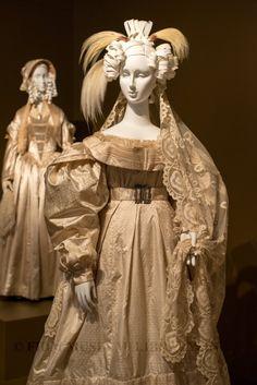(foreground) Circa 1828 silk jacquard and aerophane Wedding Ensemble; (background) Circa 1845 silk satin, organza, and braid Wedding Ensemble.  Via FIDM Museum.