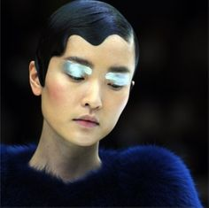 "How striking is this shot from Prada's Spring 2011 runway show? This picture is such a great representation of Prada's brand.The finger waves give it a classic look while the makeup and strong brows give it a futuristic twist. Hairstylist, Guido Palau, said, ""Even though this look has one foot in the past, it always has to move forward, as well."" We love it, Prada!"