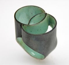 By Carola Bauer. Makes use of traditional materials and techniques, such as enamelling. Her jewelleries are constructed with an architectural approach.