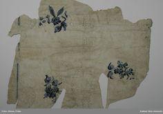 KLM 23627. Tapet, av papper. 2 st tapetbitar. Målad och tryckt. Tapet med vit limfärgbotten. Imitation av slingrande spets tryckt i grått. Vertikala streck målade i blått och blombuketter i blått, grönt och svart i rokokostil som troligen är handmålade. Pappret har som reliefstruktur. Datering: 1770-tal.