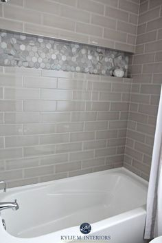 Bathroom with bathtub and gray subway tile shower surround with niche or alcove in hexagon marble tile, greige accent tile. Kylie M Interiors design #tilebathtub
