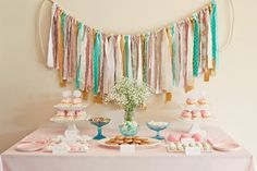 Soft sweet light pink blue first birthday party dessert table featuring fabric tassel garland backdrop