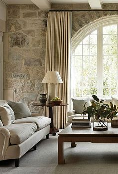 Interior design inspiration from a family room designed by Phoebe Howard with limestone wall magnificent arched window and white decor.