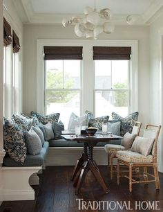 A banquette cozies up to the windows in this multi-purpose nook. - Traditional Home ® / Photo: Eric Roth / Design: Daniel Reynolds