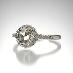 An 18k white gold setting for a 6mm rose cut diamonds = 0.45cttw, surrounded by a halo of brilliant diamonds = 0.34cttw. Size 6.