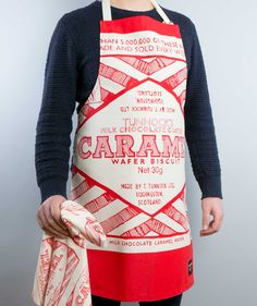 """This apron celebrates the iconic foil wrapper of the world famous Scottish biscuit. Tunnock's describe it as """"the national treat"""" and I completely agree. From Gillian Kyle's Tunnocks Collection it makes a unique Scottish gift and is great for brightening up your kitchen (and your mood)! Have a look at our whole Tunnock's Caramel Wafer Collection."""