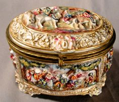 A19th Century Capodimonte high relief porcelain, hinged oval shaped footed box with overall pastoral and putti decoration, hand painted with gilt ormolu fittings