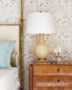 We love the hand-drawn quality of this whimsical wildflower botanical wallpaper. The spare look lets the hammered finish of the brass bed and marquetry side table shine. | Photographer: Donna Griffith Designer: Theresa Casey