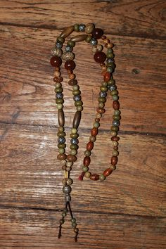 Necklace with beige/green Sandalwood beads, brown & khaki wood beads, Bodhi seeds, silver spacer beads, Bamboo tubes & silver Tibetan Guru beads. 30 €