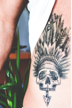Skull, feather headdress, arrow tattoo design