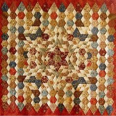This quilt was made by Kay Haydon and is English paper pieced and hand quilted.