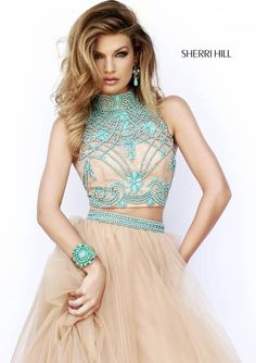 Sherri Hill Semi Formal Dresses #11225 Our favorite exquisite all-over stone work lays beautifully on this nude lace cropped bodice. The same beading lines the thin waistband of the tulle ball gown skirt.