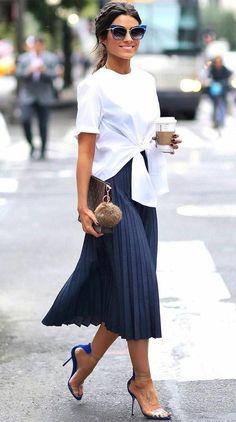 Office look descolado: 8 ideias para experimentar agora. T-shirt branca com nó na cintura, saia midi plissada, sandália de duas tiras
