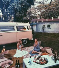 Outdoor picnic on blankets and Aztec geometric pillows next to a pink camper VW Volkswagen bus with string lights Bohemia bohemian gypsy hippie life