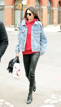Out in New York City wearing a red hoodie sweatshirt layered under a denim jacket with leather leggings.