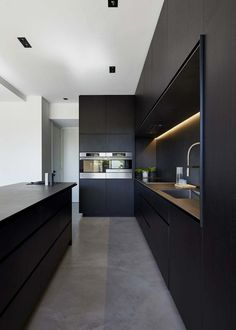 kitchen idea - M House is a minimalist house located in Melbourne, Australia, designed by DKO. The kitchen space features blacked out custom cabinetry with a black kitchen island that allows for seating and serving. Modern Kitchen Cabinets, Modern Kitchen Design, Interior Design Kitchen, Kitchen Designs, Kitchen Contemporary, Modern Design, Room Interior, Kitchen Industrial, Mansion Interior