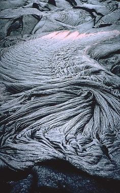 """Pahoehoe, meaning """"smooth, unbroken lava"""" in Hawaiian, is basaltic lava that has a smooth, billowy, undulating, or ropy surface. These surface features are due to the movement of very fluid lava under a congealing surface crust. Here, at the Kīlauea volcano, Hawaii, United States."""