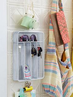 Hang a wire mesh utensil organizer near your door as a hub for keys, sunglasses, and other essentials. Use nails with small heads (that fit through the mesh of the organizer) and hang it. Let the nails stick out far enough from the wall so that you can also use them as key hooks.  /