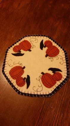 """This is a new design handcrafted candle mat. The backing is black that has a blanket stitch to a tea dyed cream top. I have hand cut black crow and pumpkins with a vine. All handsewn. This mat is 11"""""""