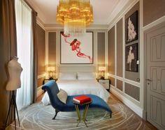 Cabeceira e criados com design simples ao lado de uma encantadora espreguiçadeira e um lustre que é um escândalo , dão a este quarto muito glamour