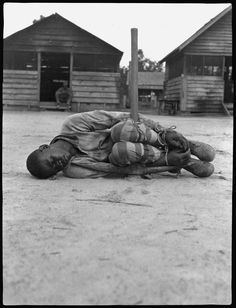 This photo of a man tied to a pickax shows a typical punishment for blacks living in forced-labor camps in the early 1930s.