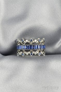 FINE JEWELRY - SALE 2624B - LOT 469 - 18KT WHITE GOLD, SAPPHIRE, AND DIAMOND BAND, FRED LEIGHTON, CHANNEL-SET WITH EMERALD-CUT SAPPHIRES, CIRCULAR-CUT SAPPHIRE AND FULL-CUT - Skinner Inc