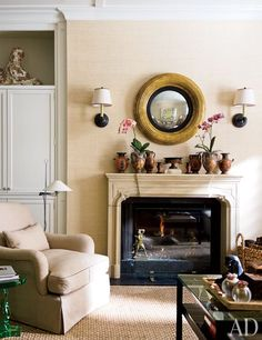 Greek vessels top a limestone mantel in the sitting area off the kitchen; the armchair and bull's-eye mirror are by Rose Tarlow Melrose House, and the floor lamp and sconces are from Circa Lighting.