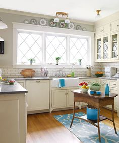 Cabinets with brushed-on milk paint, tile with a crackled ivory finish, plus honed granite and a flea-market table give the new kitchen a softly aged look.