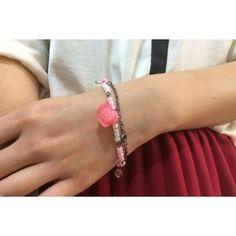 Handmade black metal bracelet with pink and white plastic beads and pink plastic beads and a pink plastic rose
