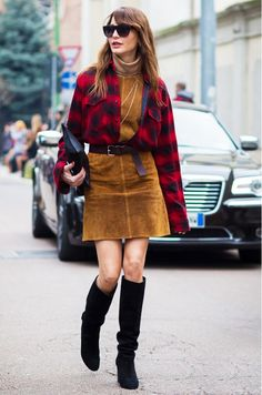 This suede turtleneck dress is paired with a red plaid button up, brown belt, and black knee high boots.