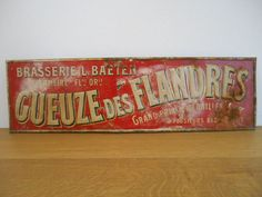 Metal advertising sign for Gueuze des Flandres from 1920 Brewery L. Baeten from Overmeire (Belgium) was active from 1892 to 1940. The sign is almost 100 years old and shows clear signs of age (the original and swivelling metal mounting eyelet is still present).  The typical Belgian Geuze beer (or Gueuze in French) is a murky, golden to amber, sparkling drink with a complex sour to bitter taste and sour acidic smell. It has an alcohol content of 5% to 8% and about 0.2% sugar remains after…