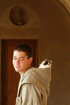 A young monk with kittens in his hood. What an unexpected photo!