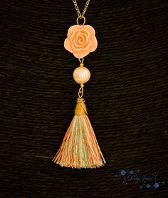 Es un collar con cadena chapada en oro, borla de hilo de seda de colores rosa perla, verde claro y naranja claro. Una rosa de resina color rosa claro y una perla de río cultivada.Se puede hacer el largo que tú desees. Hago envíos a todo el mundo. Si tienes alguna pregunta, no dudes en