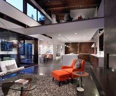 Modern open space living room with loft bedroom above. Whites and browns make the orange chair pop.
