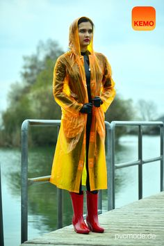 PVC Regenmode gibt's bei kemo-cyberfashion.de  Das Model trägt ein klassischen langen PVC Regenmantel in transparent orange.  PVC Raincoat transparent orange.