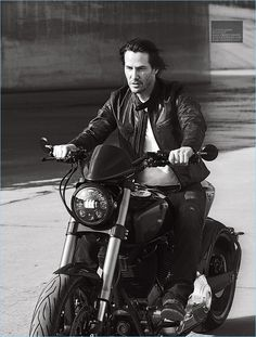 Riding a motorcycle, Keanu Reeves rocks a t-shirt and leather jacket by Belstaff.