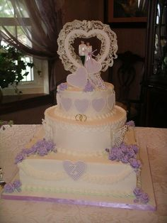 Butterflies on the lavender - Golden anniversary cake designed to mimic the couple's wedding cake. Fondant hearts and roses w/royal details.  Royal butterflies. Vanilla w/strawberry filling covered w/buttercream.  Topper was the original used at the wedding!