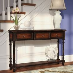Instantly elevate your favorite aesthetic with this handsome three-door wood console table. Its turned legs and metallic ring pulls add a refined touch to your decor while its rich cherry finish pairs perfectly with crisp white wallpaper for a lovely contrast. Add this piece to the entryway to anchor a timeless traditional ensemble, then top the piece off with a sleek curved ceramic table lamp and a trio of bird statuettes for an understated and dynamic vignette. Adorn nearby walls with…
