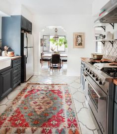 Modern spacious kitchen with warm tones and a pop of red as an accent color. by Melina Divani http://decoholic.org/2017/04/30/spanish-influence-modern-flair/