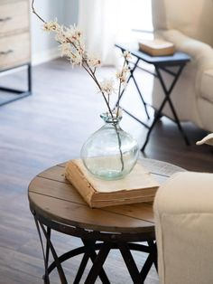 A delicate branch of flowers in a glass vase  sits on top of a wood and metal side table in the living room of the Gaspar home, as seen on HGTV's Fixer Upper.