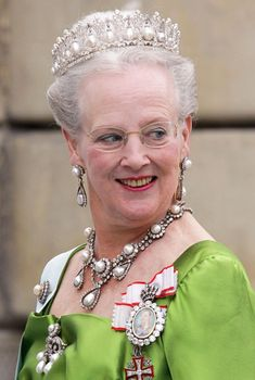 Queen Margrethe wearing the Pearl Poire Tiara. it was probably made around 1825 in Berlin at the request of King Friedrich Wilhelm III of Prussia, as a wedding gift for his daughter Louise, who was marrying Prince Frederik of the Netherlands. It includes 18 drop pearls (poiré pearls) dangling from a structure of diamond arches.