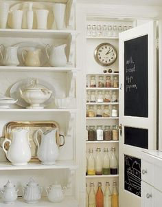 white pitchers, silver trays, chalkboard door, clock in pantry, glass food storage.  yes, please.