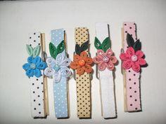 Prendedores de madeira, decorados com tecido poá, estampado ou liso, com flores em quilling. R$1,50