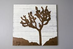 drawing your own joshua tree on hardwood using contact paper to mark out the area you want left wooden.