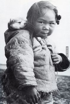 A young Inuit girl and her Husky pup.