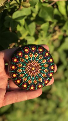 Beautiful round stone (2 3/4 inch diameter) painted with bold deep colors of reds, orange, emerald green and yellow. This stone is hand painted with an original mandala dot art design. The design is painted using high quality acrylic paints then sealed multiple times with a