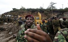 A policeman controls the crowd gathering at the scene of a landslide in Mathare valley slum after boulders, rocks and mud tumbled down a hillside overlooking the slum, smashing into the houses and burying the occupants in Kenya's capital Nairobi. (Reuters)