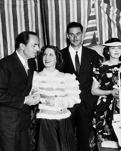 William Powell, Norma Shearer, Errol Flynn, and Kay Francis at a party.