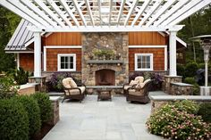 A Traditional patio for a country home includes stone benches around the parameter, a hearth fireplace and built=in BBQ Grill Kitchen out of the way to the right. The pergola can be decorated for special occasions & a canopy can add shade then removed fo laundry or seasons